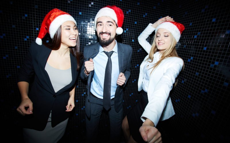 Portrait of cheerful business group in formalwear and Santa caps dancing in night club